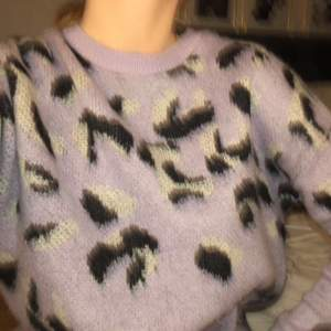 Stickad tröja i lila med leopard mönster! Endast använd 1 gång eftersom tröjan är lite för kort i armarna. Tröjan är i fint skick.