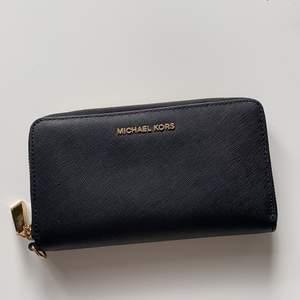En äkta svart Michael Kors plånbok. Rymlig med många kort & kontant hållare. Köparen står för frakten . Nypris 1700kr