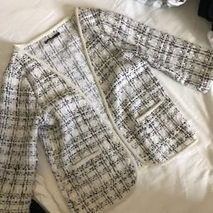 En kontorskofta. I vit och svart mönster. I samma modell som en Kavaj men utan knappar. Sitter bra och har rymliga fickor. En trekvartslång ärm och fin champengefärgad kantz