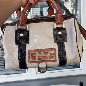 En glansig guess väska med krokodil skin och har även ett längre band som man kan ha över axeln ! Orginalpris : 1000kr, Jävligt bra kap!!