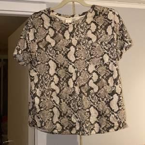 Ormmönstrad tröja med en ficka på bröstet. Aldrig använd. Slutsåld på hemsidan, storlek M. Säljer för 60kr frakten ingår i priset!