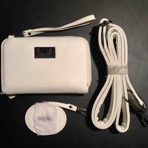 Säljer min Lissa Wang universal hand/axelremsväska i färgen vit croc. Väska med innerfack för mobilen, 3st kortfack och fack för sedlar. Avtagbar handledsrem, bred axelrem och smal axelrem. Aldrig använd, fått en liten fläck därav priset. Nypris: 199 kr