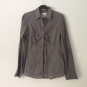 Skjorta som är figursydd, därav rymligare med tyg fram för bröst och smalare midja. Väldigt fin med alla dubbel knappar! Priset är förhandlingsbart.