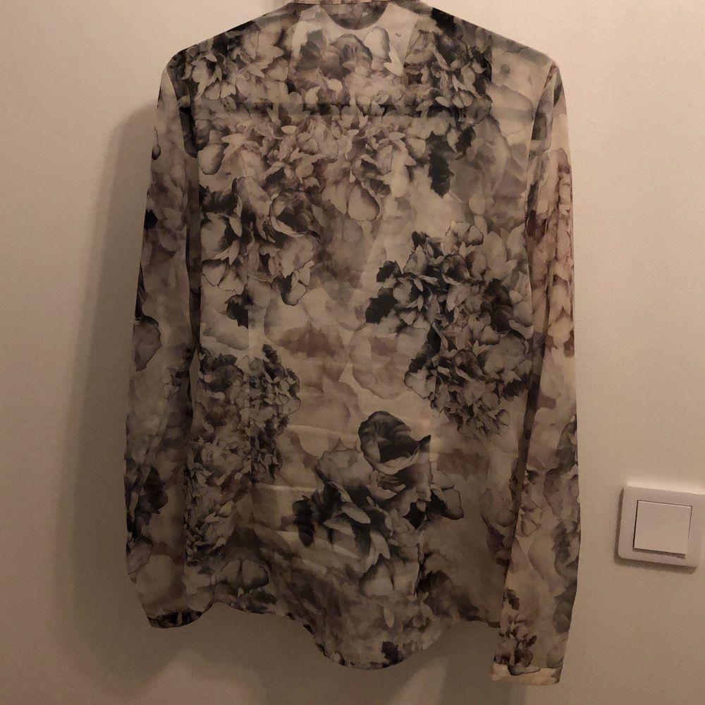 En grå/vit blus från H&M med omlott och rynk nedtill. Fin passform😍👌🏼 Lite längre baktill. . Blusar.