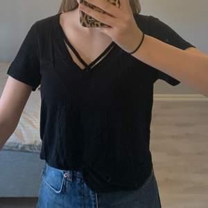 Fin svart t-shirt med två band vid urringningen. Oanvänd!Nypris: 250kr.     Mitt pris: 75kr.