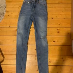 jeans med hål på ena knät och slitning på andra benet. storlek xs men skulle kunna passa s