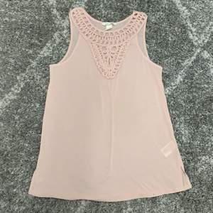 Ljus rosa linne med snygg detalj längst med halsen.