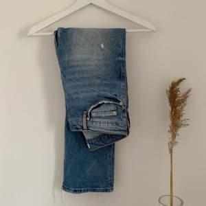 Så fina jeans ifrån Zara. Jeansen har hål på båda knäna och lite slitningar , råa kanter och är i en mellanblå tvätt. I gott skick!!  Köparen står för frakten!!