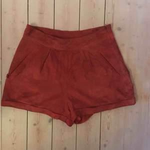Röda mocka-shorts från TopShop. Snygga till t. ex vitt linne. Skick: SLITNA. Dragkedjan trög och shortsen sett bättre dagar. Köpt på myrorna i Stockholm i samma skick. Dock 100% läder på utsidan och sjukt coola shorts, och priset ⤵️