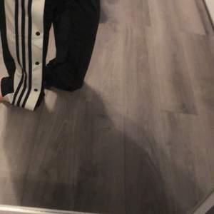 (köpta för: 900kr) dessa är ett par svarta Adidasbyxor med svarta ränder och svarta knappar (som går att knäppa upp hela vägen upp). dessa är lite för långa för mig och jag är 160cm lång. dom är jättefina och jättesköna men har bara använt dom 1 gång eftersom att dom är för långa. (ungefär 5cm) för långa. pris kan sänkas