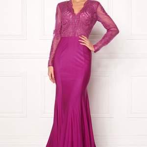 Balklänning i stark rosa färg. Nederdelen är stretchig och toppen är i spets. Bältet ingår inte. Helt ny! Kostar 3499:- ny