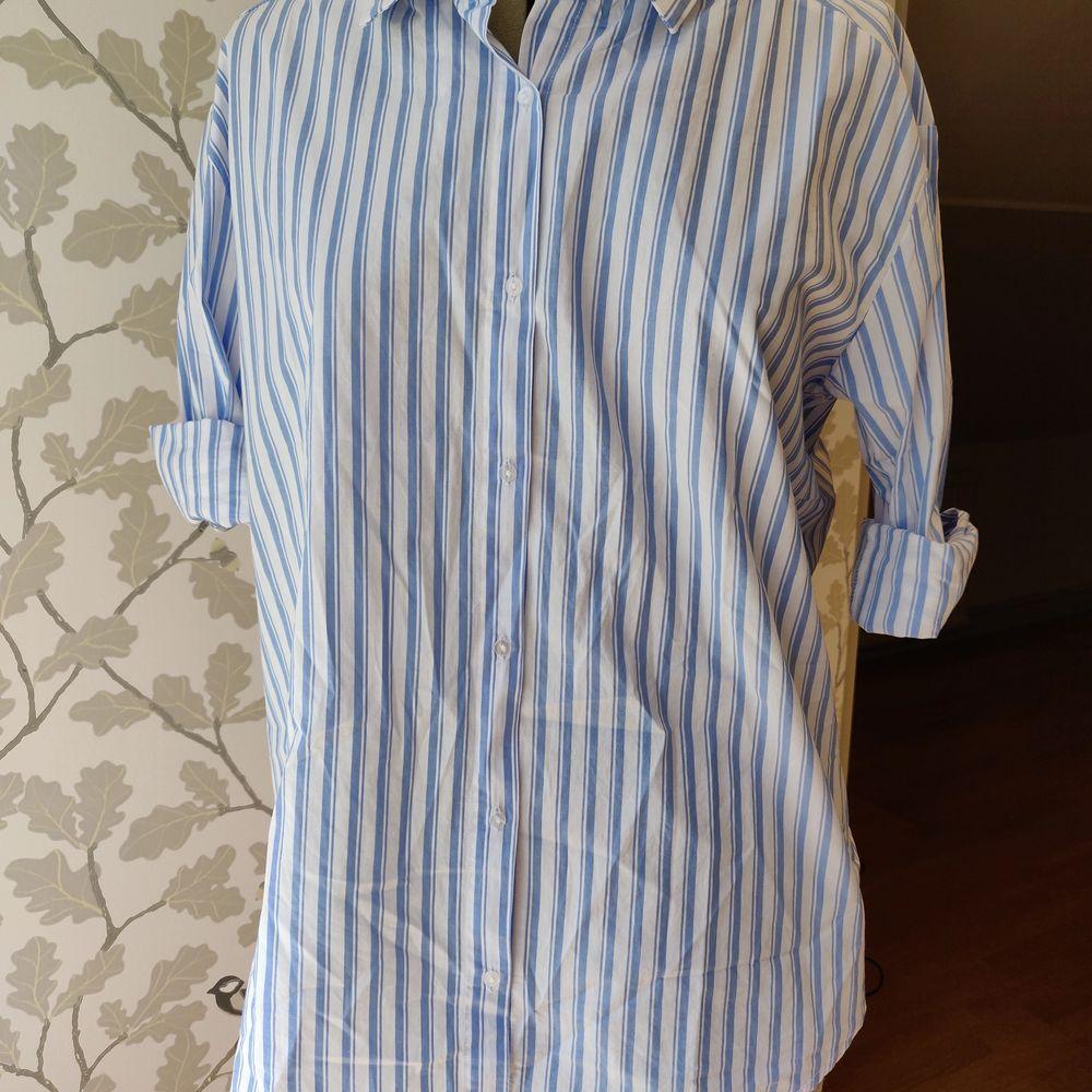 Mångfuktionabel skjorta från Nelly trend, blå vit randig, helt oanvänd där av lappen kvar. Skjortor.