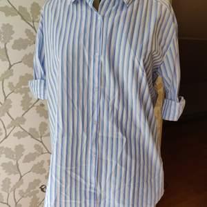 Mångfuktionabel skjorta från Nelly trend, blå vit randig, helt oanvänd där av lappen kvar