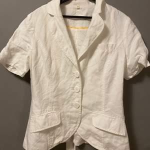 Säljer denna vita kortärmade skjortan, den knäppas av 3 knappar med en figurform