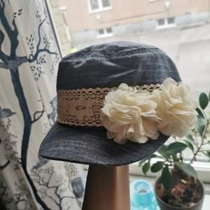 En söt liten och mjuk jeans keps med en vit-blommig detaljering vid sidan. Riktigt gullig och knappt använd.