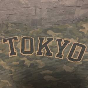En militär tröja med dragkedja. Det står Tokyo bakom.