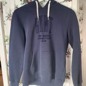 En jättefin mörkblå hoodie från Gant i storlek S. Hoodien har en rosa inuti luvan. Tyvärr ger inte kameran färgen på hoodiens dens rättvisa, på bilder ser färgen lite ljusare ut än vad den egentligen är. Hoodien är i bra skick!