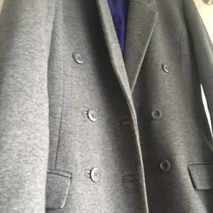 Ursnygg grå trendig kappa som knappt är använd! Sitter tight och formar kroppen snyggt! Inga skador, som ny!