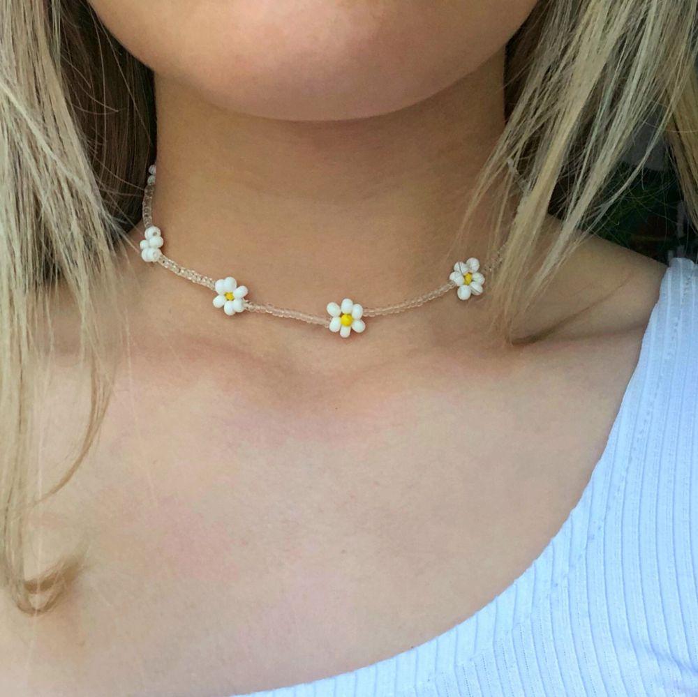 Ett pärlhalsband med vita blommor. Super fint till sommaren! Bra kvalitet och töjbar tråd. Skriv om du vill att jag ska göra halsbandet kortare/längre. 11 kr frakt☀️💕☀️💕. Accessoarer.