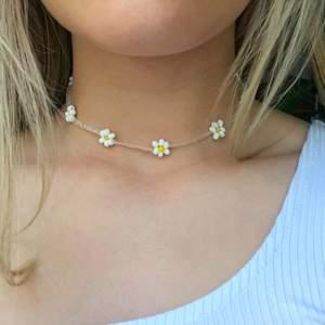 Ett pärlhalsband med vita blommor. Super fint till sommaren! Bra kvalitet och töjbar tråd. Skriv om du vill att jag ska göra halsbandet kortare/längre. 11 kr frakt☀️💕☀️💕