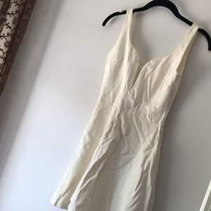 Vit kort klänning med bygel i v-ringningen. Figursydd i lite tjockare tyg. Endast använd en gång. Köpt i USA. Märket är Solemio LA. Storlek framgår ej, men passar XS/S. Köpare står för frakt.