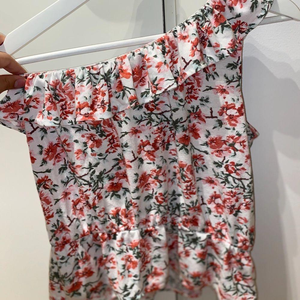 Blommig one shoulder topp med volanger över brösten och midjan Kontakta mig vid mer frågor eller bilder (frakt ingår). Toppar.