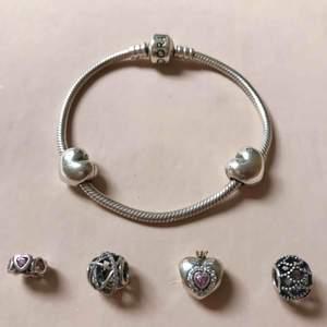 Äkta Pandora armband med två stopp och fyra berlocker.