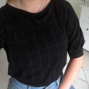 En söt svart blus i härligt material. Det är både vita och mörkblå rutor på den. Använd max fyra gånger så den är i fint skick.