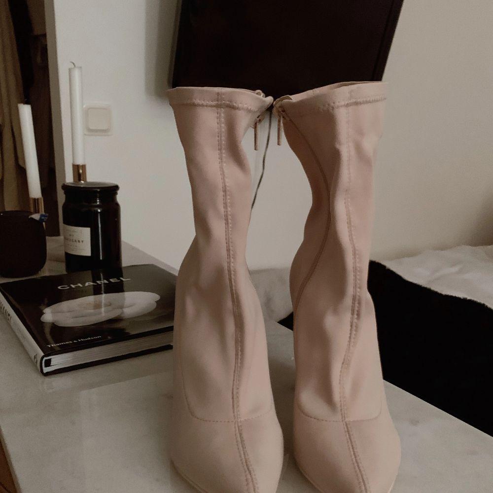 OANVÄNDA NYA beiga skor med blockklack. Stretchigt material, så sitter som en strumpa, skitsnyggt! Fungerar med ett par tighta jeans, men även med en snygg klänning. Tyvärr för stora för mig som egentligen har strl 38. Eventuell frakt betalas av köpare, annars finns de att hämta i Teleborg, Växjö.. Skor.