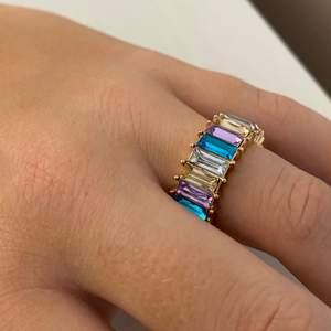 Ring med stenar i olika färger. Aldrig använd men saknas en sten. Frakt tillkommer