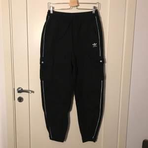 """Svarta """"cargopants"""" från adidas! Köpta på junkyard i storlek 36 (passar även 38)! Jättesköna och dom har även en vit rand längst varje ben som även har reflex-känsla som lyser upp ;)) 🌟 köparen får stå för frakt 😇"""