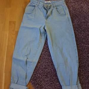 Ljusblå jeans som är pösiga i modellen. Säljer pga att dem är för stora.