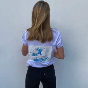 Storlek: S-L. En vit stilren t-shirt i ekologisk bomull med ett tryck föreställande havet 🌊 20% av vår vinst går till WWF🌍💙