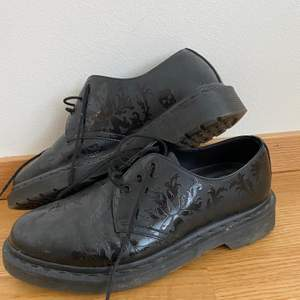 Låga Dr Martens som endast använda ett fåtal gånger. Matt svarta skor med blank matta mönster i form av skallar och krumelurer. Strl: 39 men en mycket liten sådan passar nog snarare 38 eller 37,5. Sulorna är original men lösa. Skriv gärna till mig om du har några du funderingar🥰 (vågar inte sätta något fraktpris just nu, men kollar självklar på det om någon är intresserad)