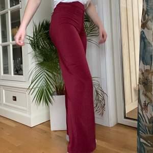 Vinröda högmidjade byxor i stretchigt tyg som använts två gånger, bootcut. Sköna att ha på sig, är dock för små för mig!