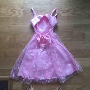 En rosa klänning för barn som passar perifer till tillställning, bröllop och liknande. Använts fåtal gånger och är i fint skick. Sidenband att knyta antingen fram eller bak. Hämtas i Kalmar.