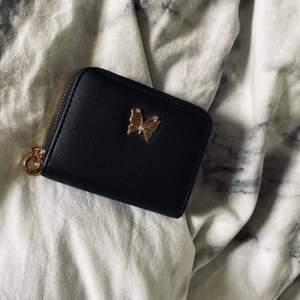 Svart plånbok med små gulliga gulddetaljer