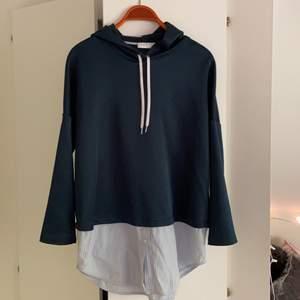 Jättefin hoodie från Sandro med inbyggd skjorta. Tyget är lite glansigt, jättefint! Knappt använd, inköpt för ca 3000kr.