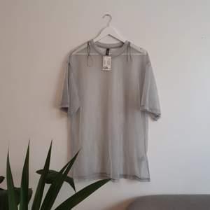 Silvrig genomskinlig T-shirt från H&M. Skimrar fint. Storlek M. Aldrig använd. Frakt tillkommer.