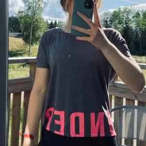 Grå träningstopp från Under Armour med rosa text som fortsätter på baksidan. Stl. XS. Helt ny med tags kvar. Betalning sker via swish. 100kr+frakt!🥰