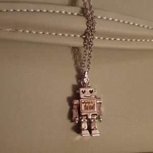 Ett silvrigt halsband med en robotliknande berlock. Säljer pga jag använder guld och det kommer därför inte till användning. Kedjan är 72cm och spännet är sönder, följer med ett extra som på bild 2. Skriv i dm vid frågor eller intresse