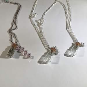 Små glasburkar med kork, väl mellan inget i eller öppen så du själv kan välja att lägga i nått, eller lavendel:) välj Vänge på halsbandet med:) OM NI VILL FÅ DEN LPPEN FÅR NI SÄGA TILL OM DET