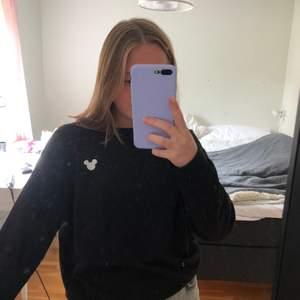 """En svart basic sweatshirt med ett litet vitt """"Musse pigg"""" märke ovanför ena bröstet. Sitter väldigt bra och skönt. Jag säljer då den inte kommit till så stor användning"""