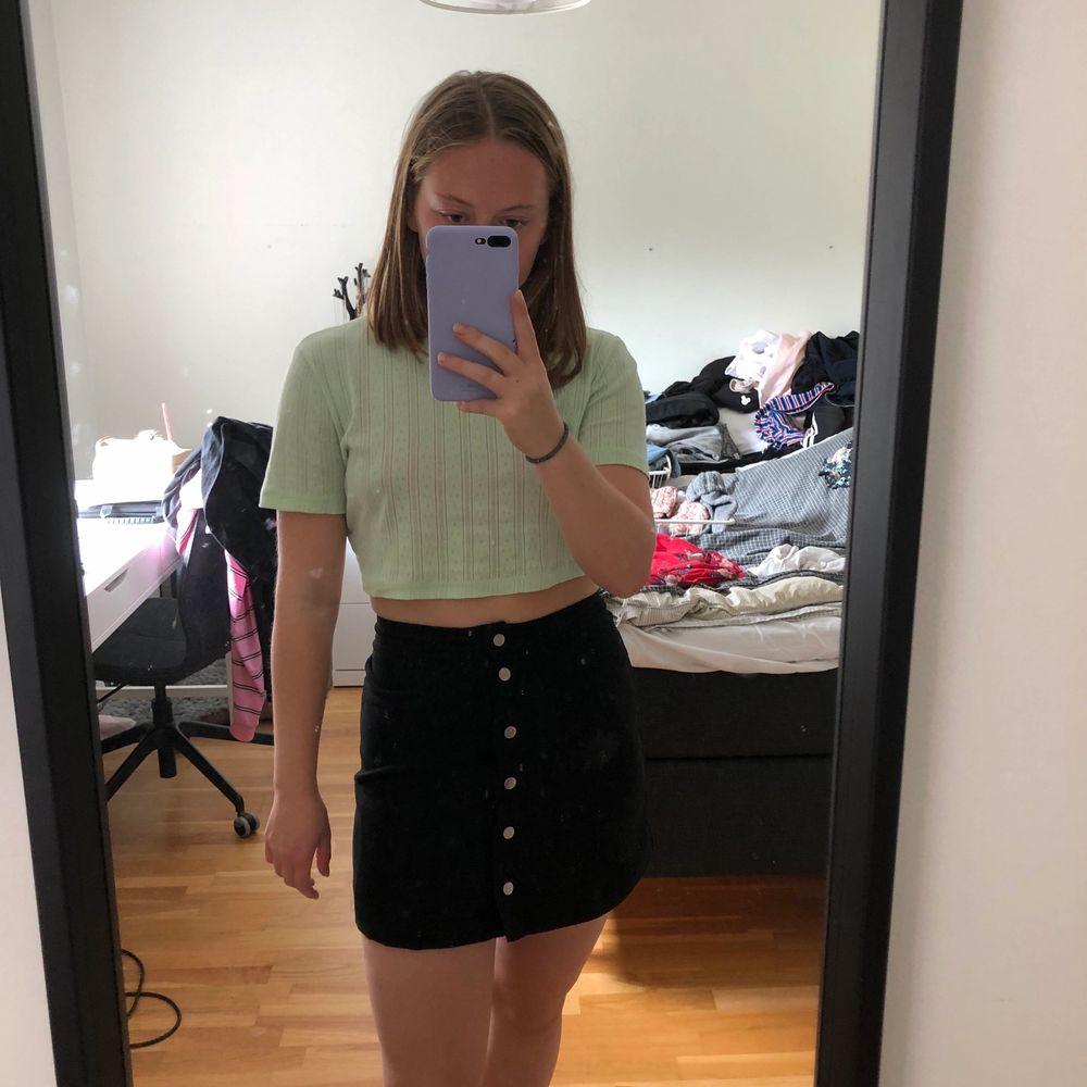 En svart kort kjol med knappar, sitter som en smäck!! Säljer då jag knappt använt. Kjolar.