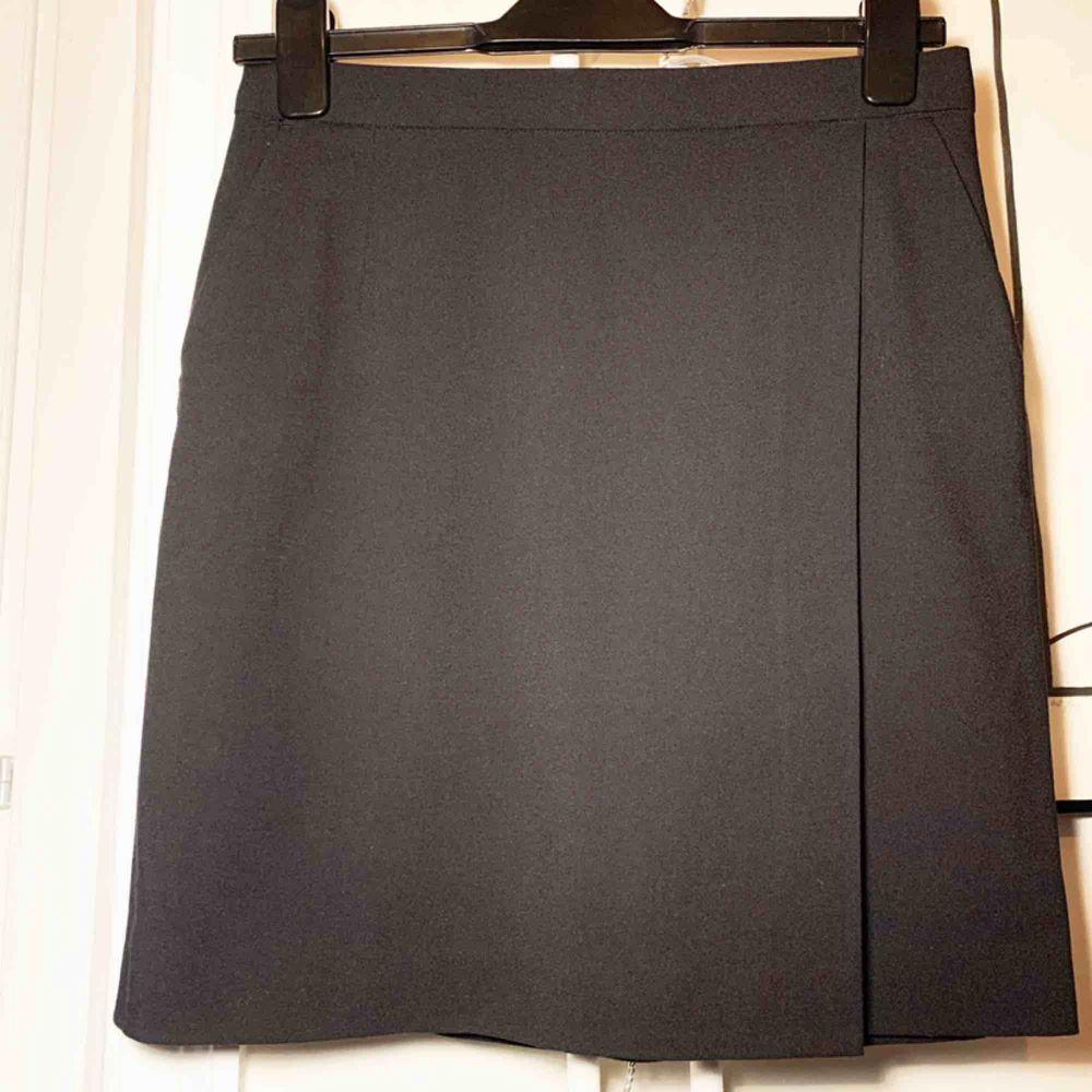Kortare pennkjol med drapering. Snygg till business men också casual. Tyget är slätt. Längd mitt bak: 48cm . Kjolar.