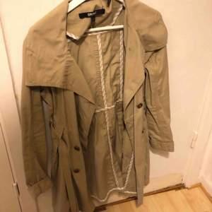 Säljer min DKNY kappa, (äkta) använd fåtal gånger. Har ett band runt midjan som går att knyta samt knappar. Färgen är lite åt det mörkare beige hållet.