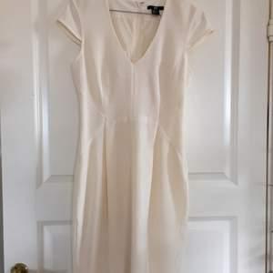 Benvit H&M-klänning i klassisk modell, med dold dragkedja bak och kort sprund.
