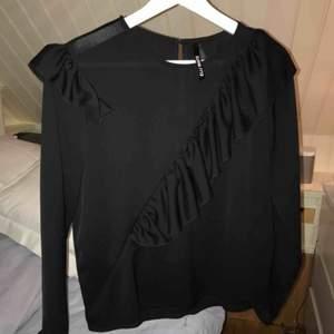 Säljer en svart blus med lite volanger, som på bilden. Var ett snabbköp och därav inte så nöjd. Osäker men antingen blev den använd den gången eller inte, sedan dess endast hängt i garderoben.  Köptes på Raglady i Frölunda.   Plus frakt