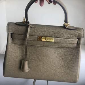 Hermes liknande Kelly väska stl 28 cm i beige färg med guld detaljer. Bag strap ingår. Oanvänd NY!!