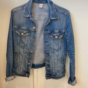 En mellanblå jeansjacka med bronsfärgade knappar. Ett litet hål som är sydd. Syns knappast när jackan är på. Kontakta gärna vid frågor eller köp :)